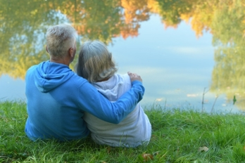Older couple sitting by a pond